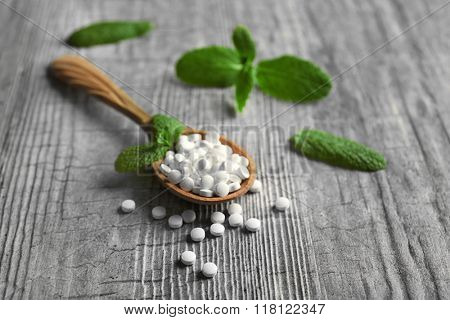 Analogue of sugar cubes and stevia  on grey wooden background
