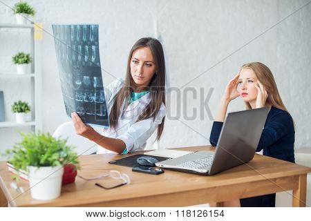Woman doctor in hospital looking at x-ray film healthcare, roentgen, people and medicine concept.