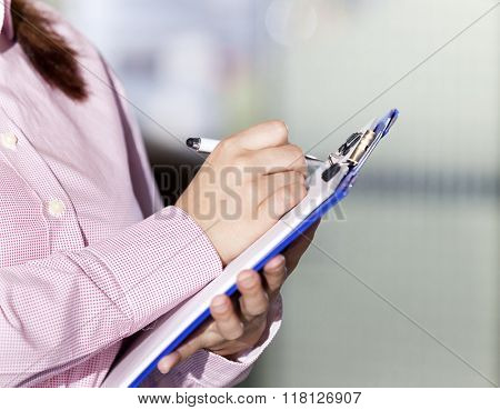 Closeup of a female engineer taking notes at metallurgy factory