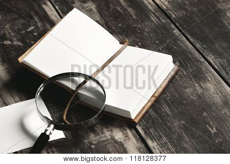 Opened Notebook, Magnifier Paper Sheet On Black Table