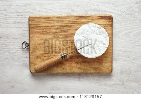 Isolated Camembert With Knife Inside On Table