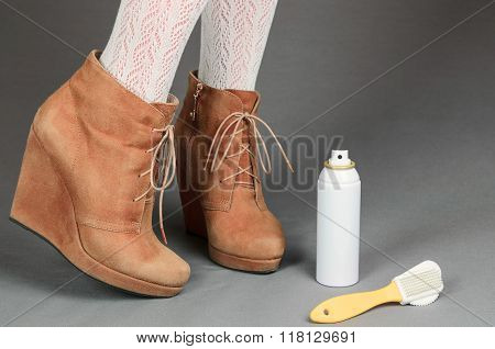 Female Legs In Brown Suede Boots On A Gray Background. Cleaning Suede Shoes