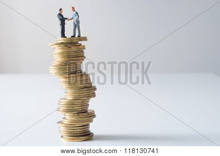 Businessmen Standing Checking Hands On Risky Coin Stack.