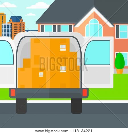Background of delivery truck with an open door and cardboard boxes in front of house.