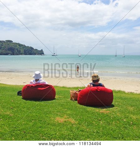 Couple relaxing on beanbags on a grassy lawn by a beach
