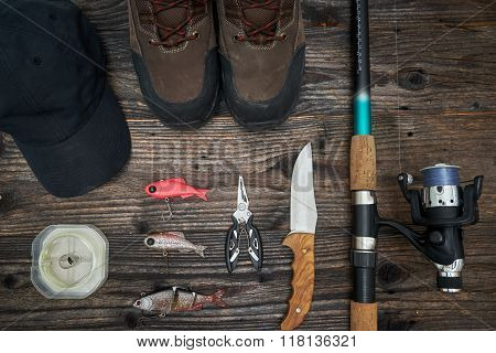 Fishing Tackles And Fishing Gear On Wooden Background