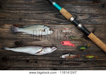 Spinning Rod, Reel And Fishing Baits Isolated On Wooden Background