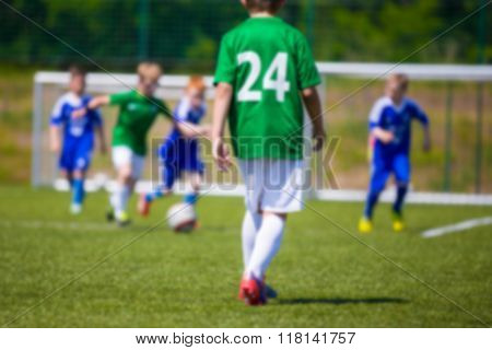 Blurred Sport Soccer Football Background. Young Boys Playing Football Match. Blue Against Green Team