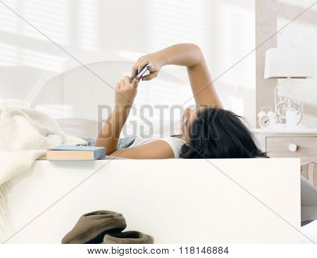 Young woman lying in bed, using mobilephone.