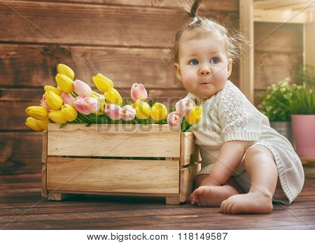 Cute child baby girl with a bouquet of tulips. Mothers day, spring concept.