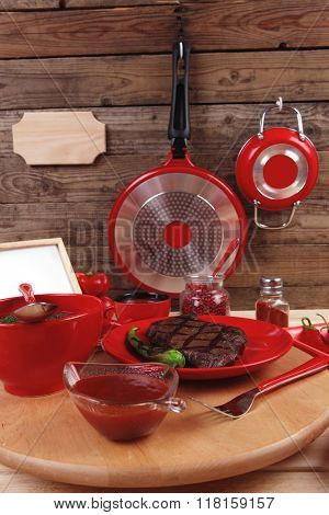 red theme lunch : fresh grilled bbq roast beef steak red plate green chili tomato soup ketchup sauce jug glass pepper american peppercorn modern cutlery wooden plate table empty nameplate menu board