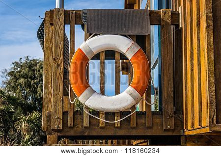 Life buoy hanging on a wooden deck. Life buoy ring on a wooden deck life saving concept in optimistic bright colors