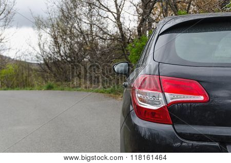 Back View Of New Black Car On Rural Road