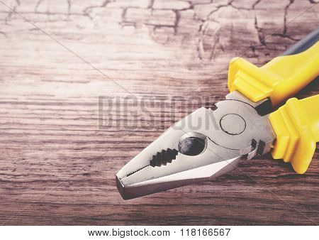 multitool pliers on wooden background