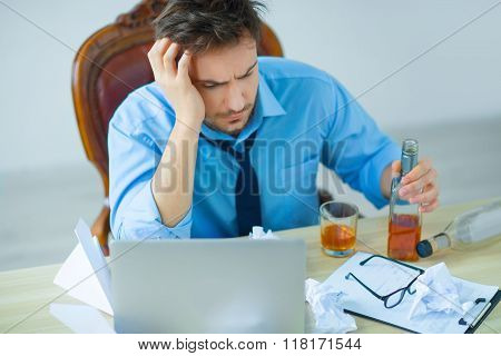 Drunk man drinking alcohol while working