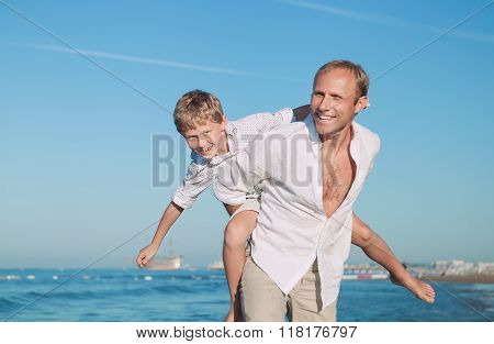 Father With Son Play Together On The Sea Side