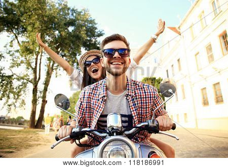 Portrait of happy young couple on scooter enjoying road trip