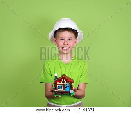 House Model In Child's Hands. Family House Concept - Portrait Of Cute Boy With A House On Green Back