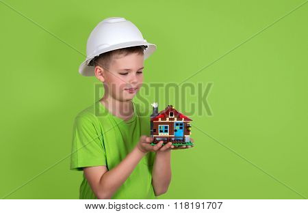 House Model In Child Hands. Family House Concept - Portrait Of Cute Boy With A House On Green Backgr
