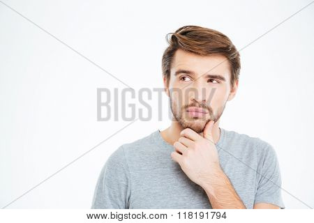 Porptrait of a pensive casual man standing isolated on a white background