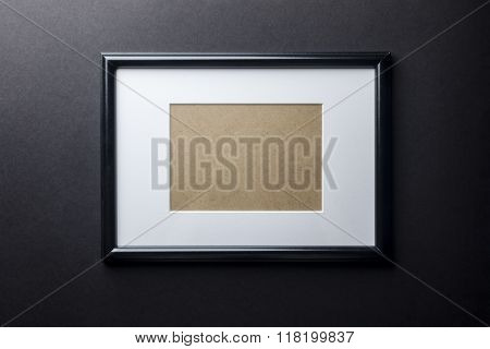 Black wood frame on black wall