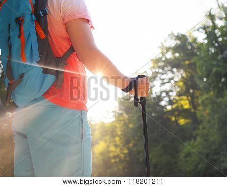 Man Hiking With Backpac And Sticks In Mountains