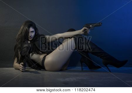 sexy, brunette girl dressed in black leather with guns and pistols in a garage, scene of action