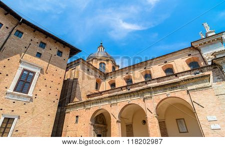 Urbino Italy - August 14 2015: Ducal Palace courtyard with tourists in Urbino Italy. The historic center of Urbino was declared a Unesco World Heritage site and represents the apex of Renaissance architecture