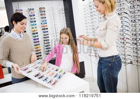 Pretty girl in optical shop choose eye frames with mother
