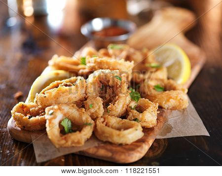 crispy calamari rings on wooden tray with lemon wedge