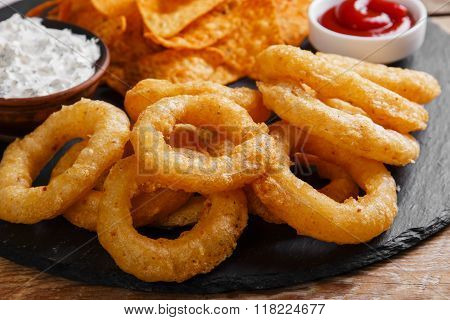 fried onion rings in batter with sauce tortilla chips