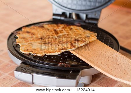 Homemade waffles in a waffle iron with wood spa