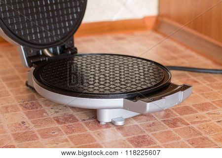 Opened waffle iron for cooking homemade waffle.