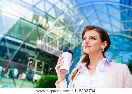 Businesswoman with coffee cup against glassy modern office build