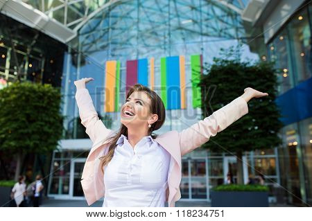 Smiling businesswoman with hands up against modern building