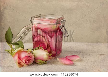 Textured still life of rose water and roses on a painterly background