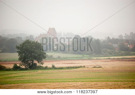 Hazy morning over the field with a church in the background