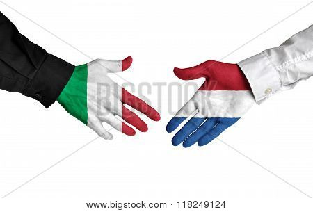 Italy and Netherlands leaders shaking hands on a deal agreement