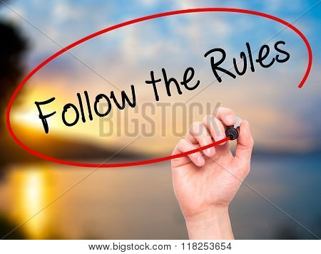 Man Hand Writing Follow The Rules  With Black Marker On Visual Screen