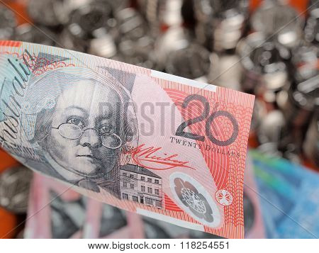 Twenty Australian Dollar Note On Front Of A Pile Of Glittering Coins