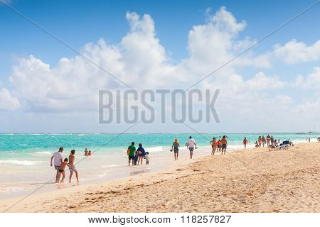 Tourists Walk Along Sandy Beach Of Punta Cana
