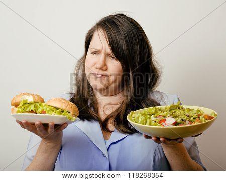 fat white woman having choice between hamburger and salad close up, unhealth fast food