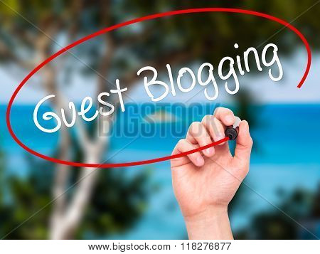 Man Hand Writing Guest Blogging  With Black Marker On Visual Screen