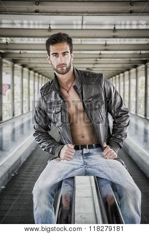 Young bearded man with jacket on naked torso