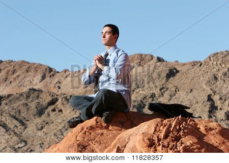 Young businessman meditating outdoors