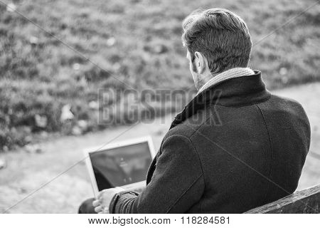 Handsome elegant businessman working in a park
