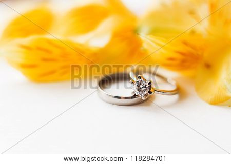 Pair Of Wedding And Engagement Rings With Yellow Alstroemeria Flower.