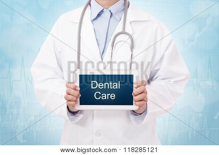 Doctor holding a tablet pc with dental care sign on blue background