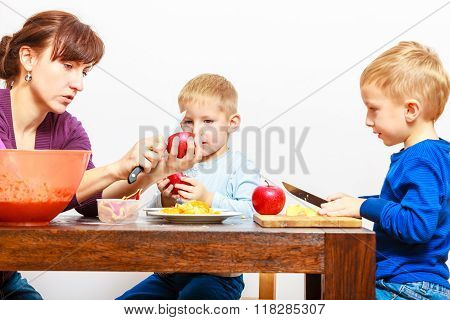 Mother With Sons Cutting Fruits Apples At Home.