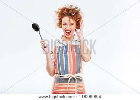 Cheerful redhead housewife with curly hair in apron holding soup ladle isolated on a white background